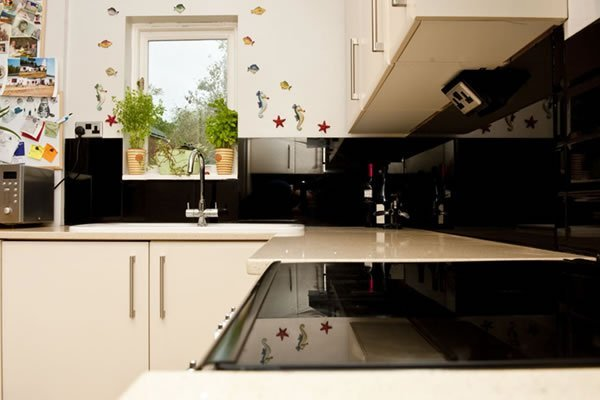 Glass top cooker breaks up the worktop and blends with the black splashback